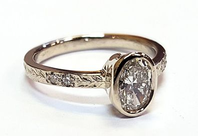 Engagement ring with a bezel set Oval diamond, and accented with a hand engraved band
